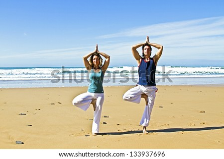 Couple doing yoga exercises at the beach - stock photo