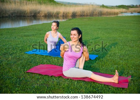 couple doing yoga outdoors - stock photo