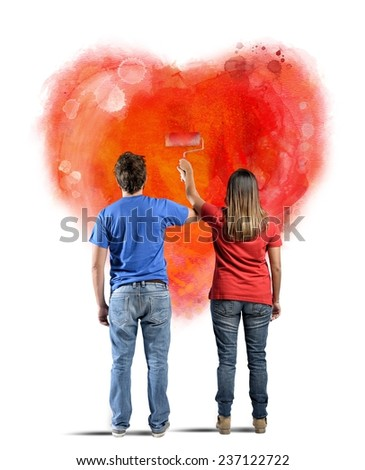 Couple drawing a heart in a wall - stock photo