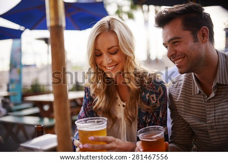 couple drinking beer at outdoor bar shot with selective focus - stock photo