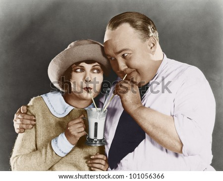 Couple drinking beverage with straw - stock photo