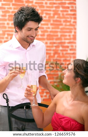 Couple drinking champagne in a restaurant - stock photo