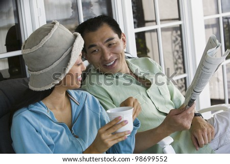 Couple Drinking Coffee and Reading Newspaper Together