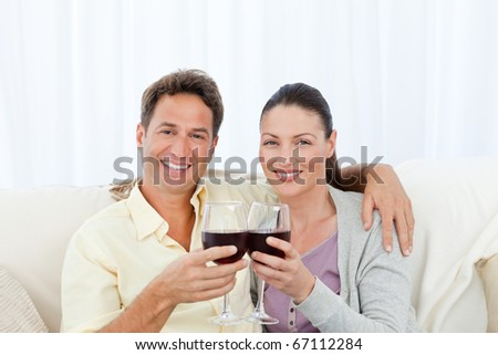 Couple drinking red win on sofa - stock photo