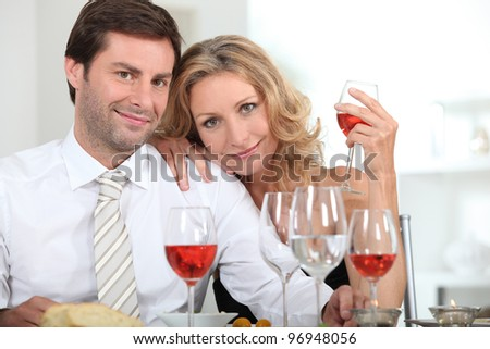Couple drinking rose at a dinner table - stock photo