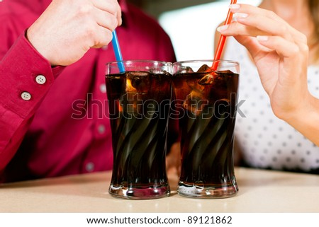 Couple drinking soda in a bar or restaurant; only torso and hands to be seen