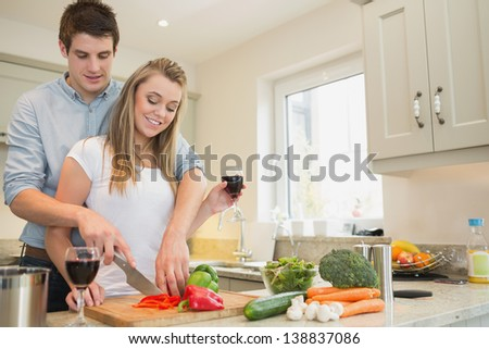 Couple drinking wine and cooking together in kitchen - stock photo