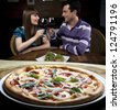 Couple drinking wine and eating pizza - stock photo