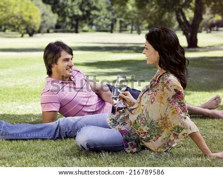 Couple drinking wine in a park. - stock photo