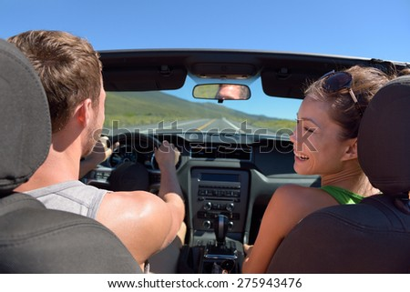 Couple driving car on road trip travel vacation in convertible. Young romantic couple on travel holidays vacation. Man driver behind steering wheel. - stock photo