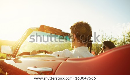 Couple driving convertible car enjoying a summer day at sunset - stock photo