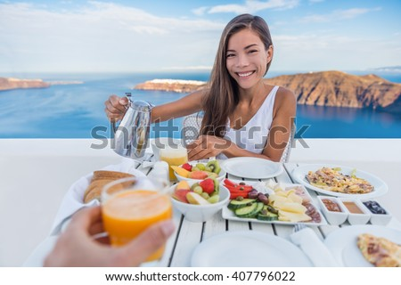 Couple eating breakfast. Smiling tourist woman drinking coffee and man drinking orange juice on terrace resort outdoor. Healthy and delicious food served for breakfast.  Santorini, Greece. - stock photo