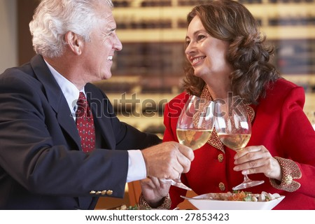 Couple Eating Dinner And Toasting With A Glass Of Wine - stock photo