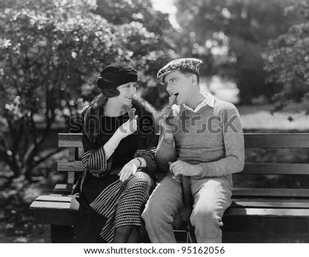 Couple eating ice cream cones in park - stock photo