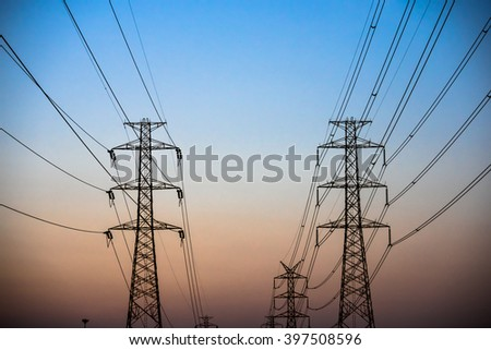 Couple Electricity pylon at sunset - stock photo
