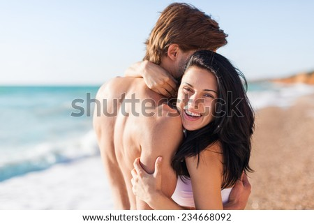 Couple embrace on beach, love laughing woman hug man happy smile sea shore romantic smiling, summer ocean vacation holiday travel - stock photo