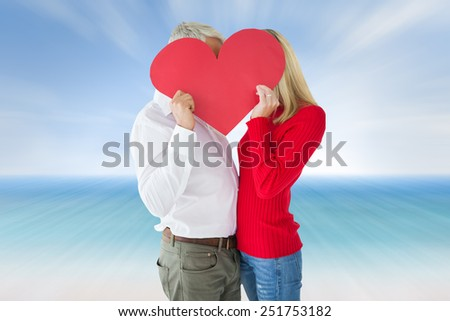 Couple embracing and holding heart over faces against beach scene - stock photo
