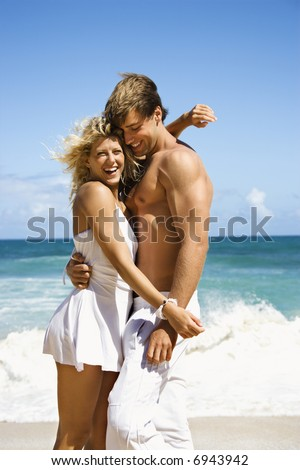 Couple embracing and smiling on Maui, Hawaii beach.
