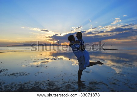 Couple embracing at a lake during an amazing sunset - stock photo