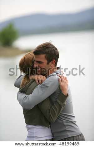 Couple embracing each other by a lake - stock photo