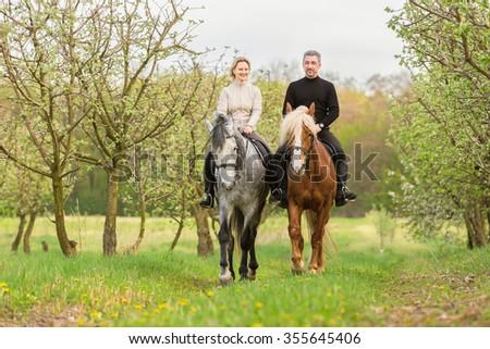 Couple enjoy riding horses in spring garden. - stock photo