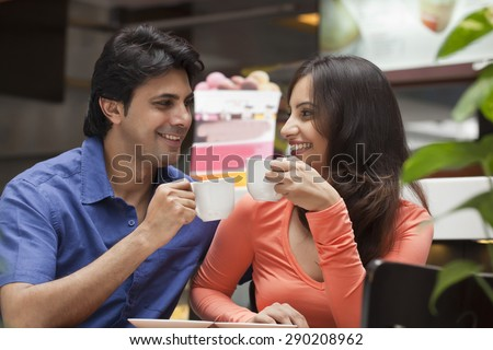 Couple enjoying a cup of tea in shopping mall - stock photo