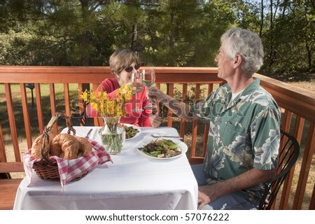 couple enjoying a dinner in an outdoor restaurant toasting each other - stock photo