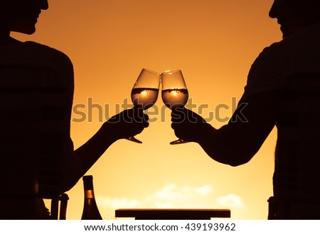 Couple enjoying a glass of wine in a beautiful romantic sunset setting. Original captured image.  - stock photo