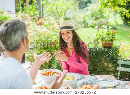 Couple enjoying a healthy lunch at a garden table Focus on the girl