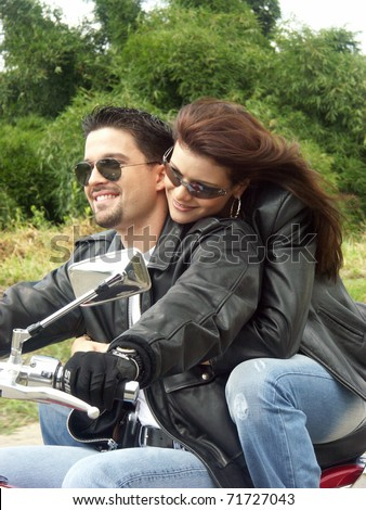 Couple enjoying a ride by motorcycle. - stock photo