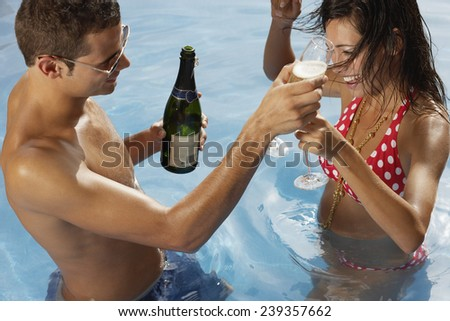 Couple Enjoying Champagne in the Pool - stock photo