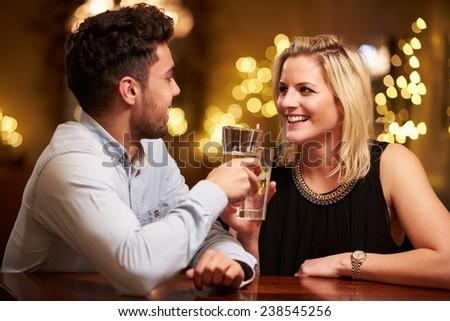 Couple Enjoying Evening Drinks In Bar - stock photo