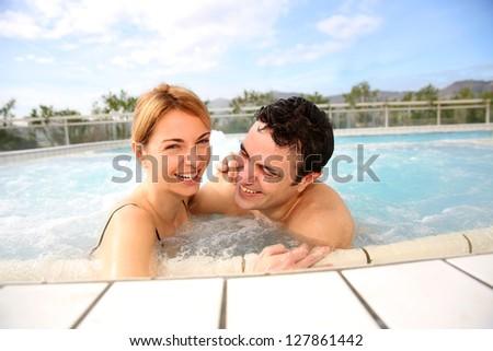 Couple enjoying jacuzzi in spa center - stock photo