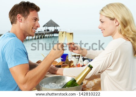 Couple Enjoying Meal In Seafront Restaurant - stock photo
