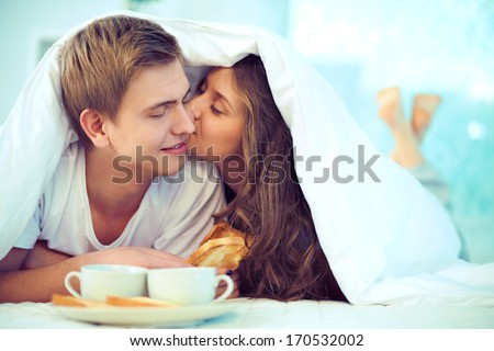 Couple enjoying one another while having breakfast in bed - stock photo