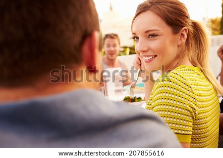 Couple Enjoying Outdoor Summer Meal With Friends