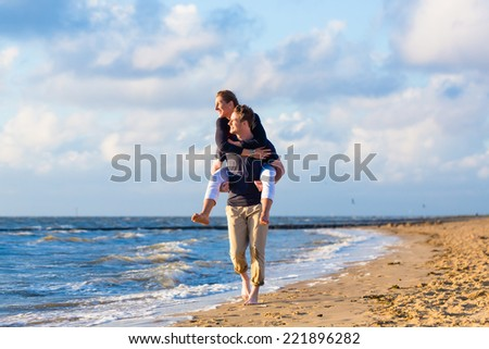 Couple enjoying romantic sunset at German north sea beach - stock photo