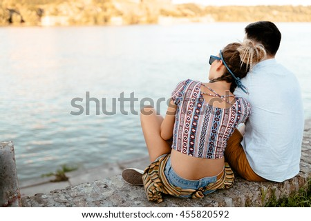Couple enjoying serene moments while staring at river - stock photo