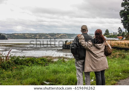 Couple enjoying the amazing view in Chiloe Island, Chile.