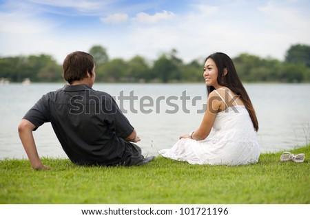 couple enjoying the day sitting at the lake - stock photo