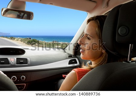 Couple enjoying their new car on a coastal road - Woman looks at man with tenderness