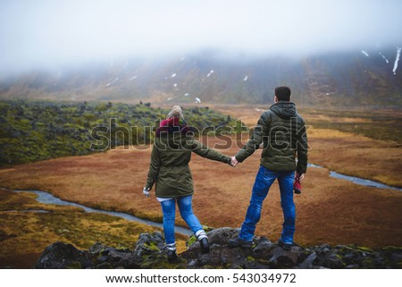 couple enjoying view on field and river