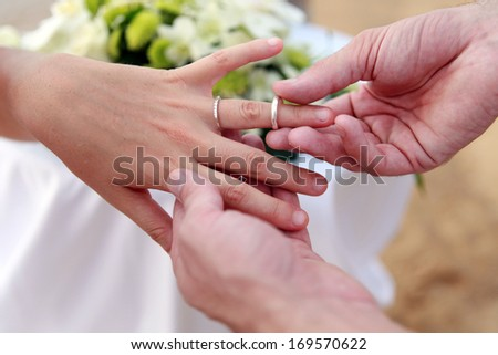 Couple exchanging wedding rings during a ceremony. - stock photo