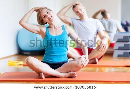 Couple exercising at gym - stock photo