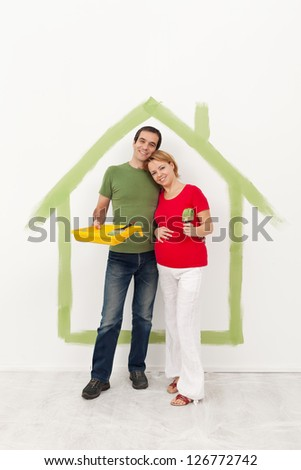 Couple expecting a baby redecorating their home - standing with painting utensils - stock photo