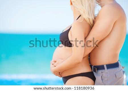 Couple expecting baby and man his fatherhood on sea background - stock photo