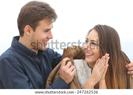 Couple falling in love with he covering her with his jacket in a cold winter outdoors - stock photo