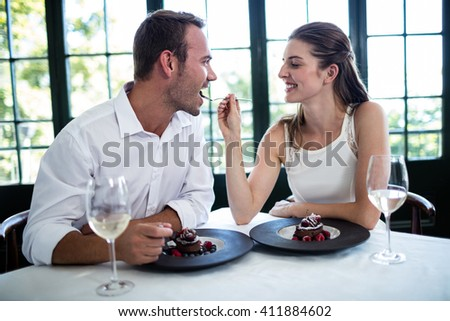 Couple feeding each other and smiling while spending time at the restaurant - stock photo