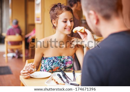 Couple feeding each other with the cake in restaurant - stock photo