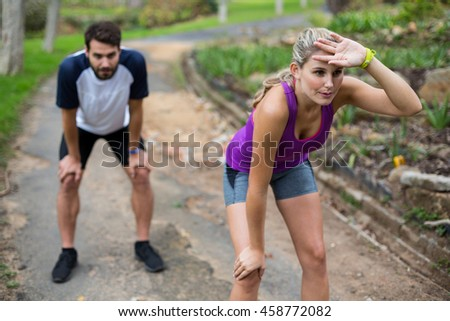 Couple feeling exhausted after jogging in countryside